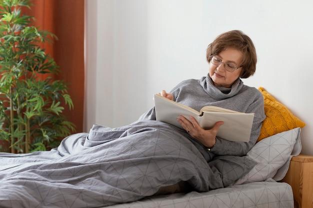 중간 샷 여자 독서 모드 침대