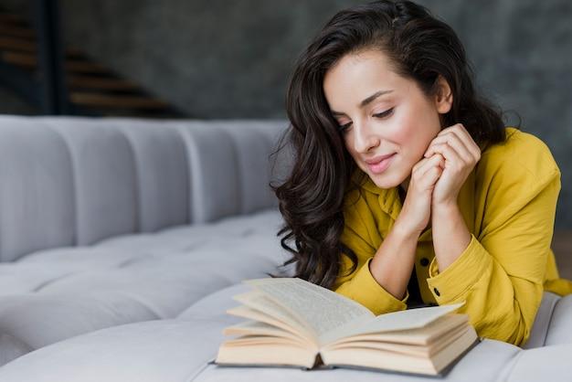 リビングルームで読書ミディアムショット女性