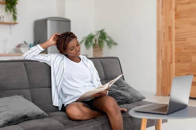 Средний снимок женщины, читающей на диване