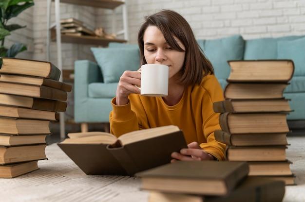 Средний снимок женщины, читающей на полу