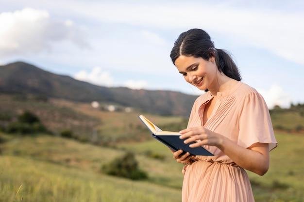Средний снимок женщины, читающей на открытом воздухе