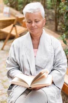 Женщина среднего кадра читает снаружи