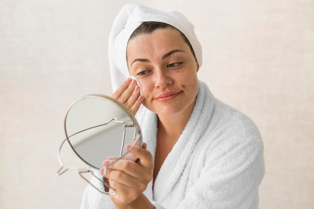 Medium shot woman removing make-up
