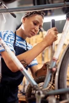 Donna del tiro medio che ripara la bici