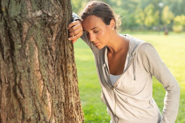 Средний выстрел женщина отдыхает возле дерева
