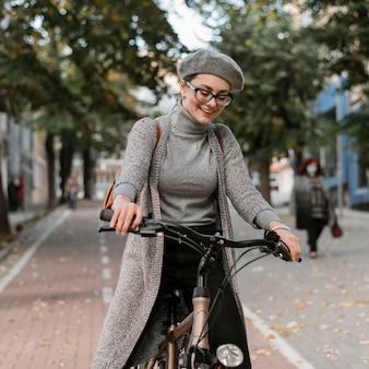 Donna del colpo medio che guida la bicicletta