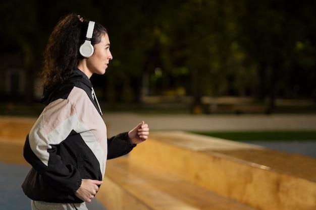 夜に走っているミディアムショットの女性