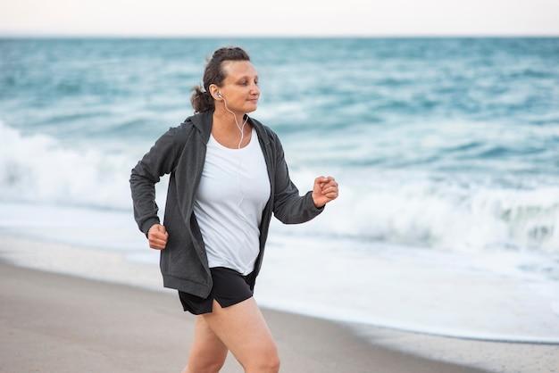 岸を走るミディアムショットの女性