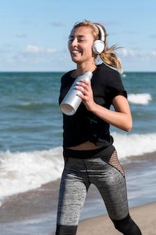 Donna del colpo medio che corre sulla riva