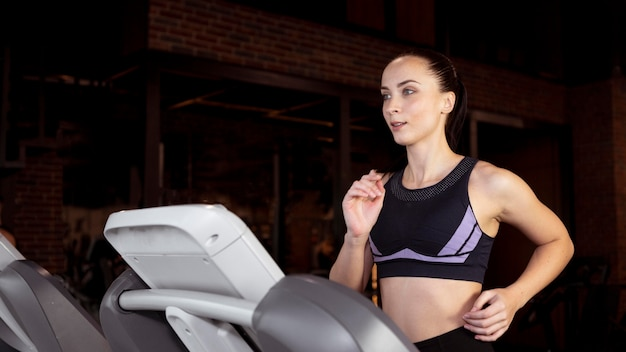 Medium shot woman running on treadmill