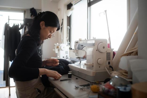 屋内で縫うミディアムショットの女性