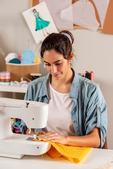 Medium shot woman  sewing with machine