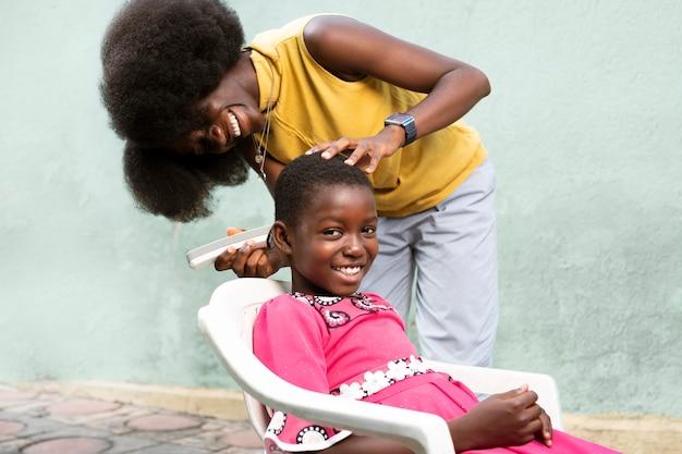 ミディアムショットの女性が女の子の髪を剃る