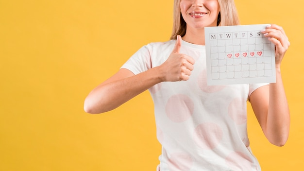Medium shot of woman showing her period calendar and thumps up