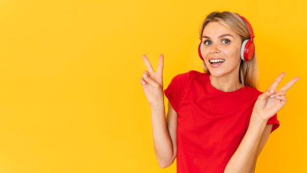 Medium shot woman showing peace sign