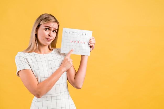 Colpo medio della donna che mostra il calendario periodo
