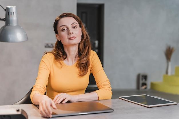 Женщина среднего выстрела, сидящая за столом