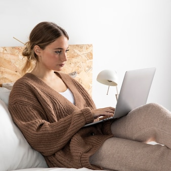 Medium shot woman sitting in bed with laptop