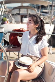 Donna del colpo medio che si siede sulla barca