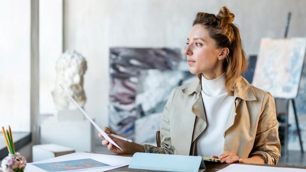 Donna del colpo medio che si siede allo scrittorio