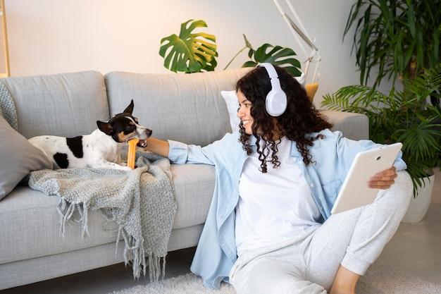 Donna del colpo medio che si siede sul pavimento con l'animale domestico