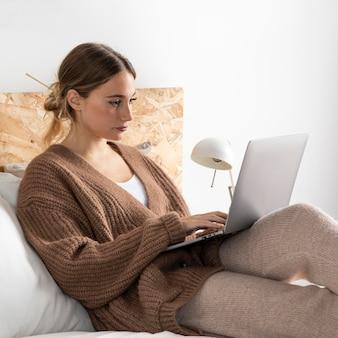 Средний снимок женщины, сидящей в постели с ноутбуком