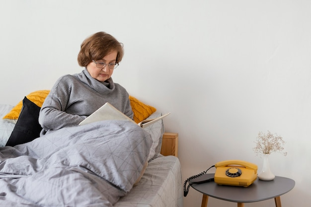 Среднего выстрела женщина, сидящая в постели