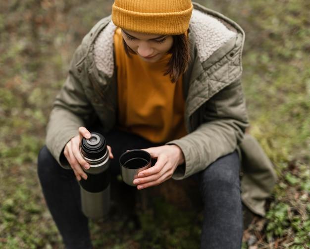 Среднего выстрела женщина, сидящая в лесу