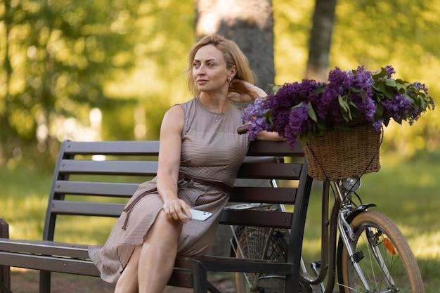 Donna del colpo medio che si siede vicino alla bicicletta