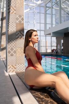 プールの近くに座っているミディアムショットの女性