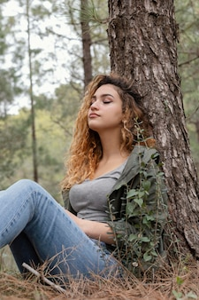 Medium shot woman sitting near tree