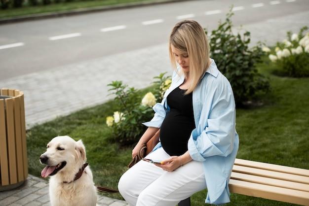 Среднего выстрела женщина, сидящая на скамейке