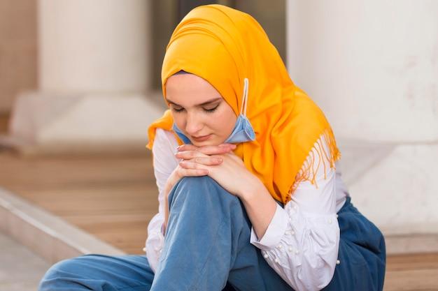 Средний выстрел женщина сидит на полу