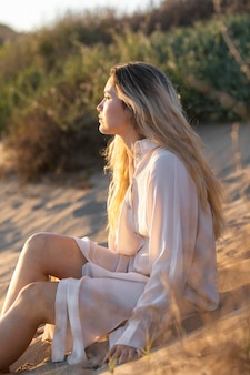 Donna del colpo medio che si siede sulla sabbia