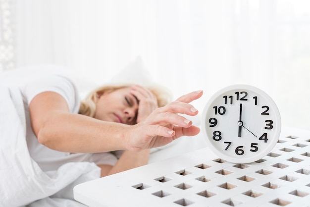 Medium shot woman sleeping with clock
