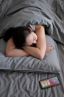 Colpo medio donna che dorme con il telefono