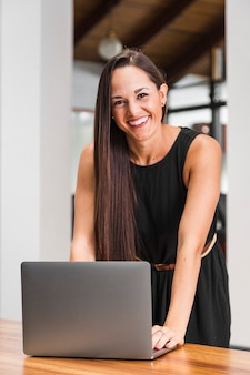 Medium shot woman smiling and working at the laptop