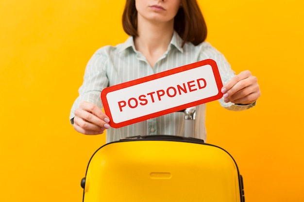Medium shot woman standing next to her luggage while holding a postponed sign
