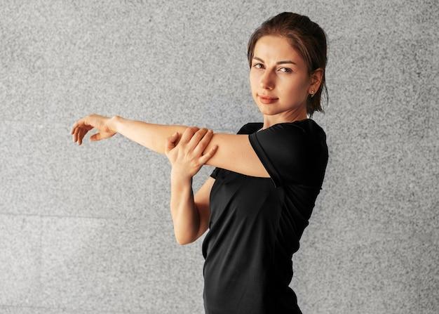 ミディアムショットの女性が腕を伸ばす