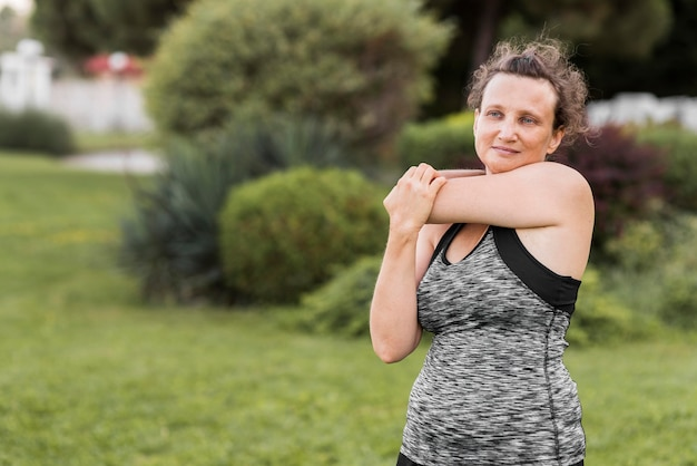 Donna del colpo medio che allunga il suo braccio