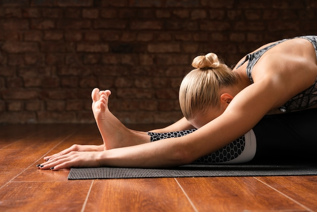 Medium shot woman stretching at home