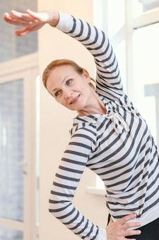 Женщина среднего выстрела, растягиваясь в помещении