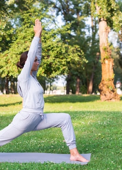 Medium shot woman stretching outdoors