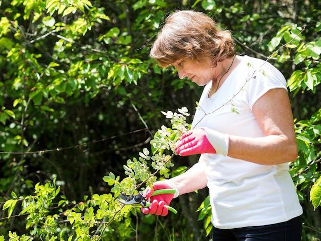 庭の世話をするミディアムショットの女性