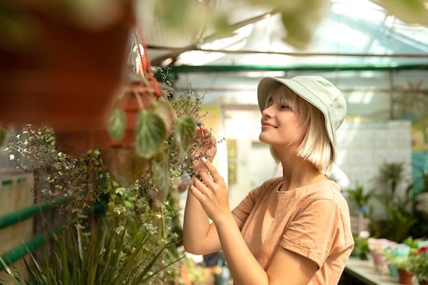 Donna del colpo medio che si prende cura della pianta