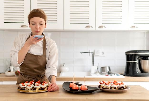 Средний снимок женщины, делающей фото десерта