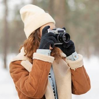 Donna del colpo medio che scatta foto nella foresta