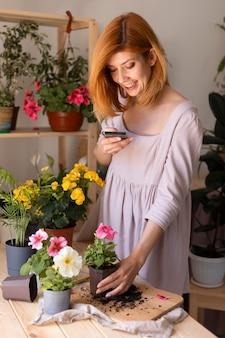 植物の写真を撮るミディアムショットの女性