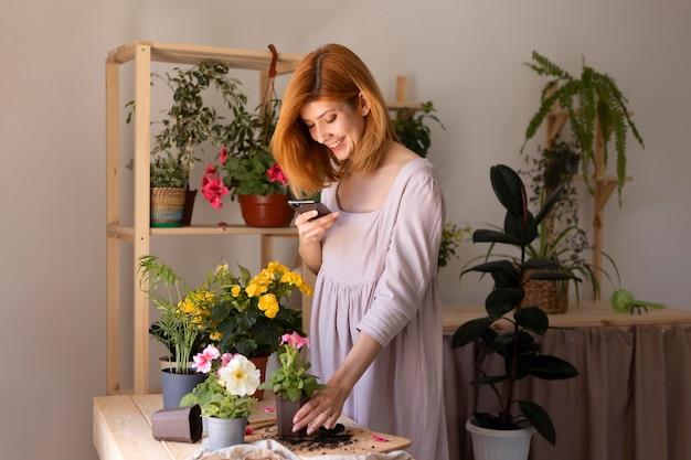 Donna del colpo medio che prende le foto della pianta