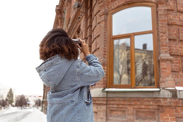 Donna del colpo medio che cattura le foto